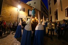 Penitents push the christ sculpture during an easter holy week procession in mallorca detail on hoods detail. Penitent push amongst the narrow streets the stock images
