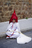 Penitent resting sitting on the ground during an Easter procession Stock Photo