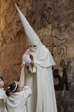 A penitent walks in front of a graffiti in the procession of Holy Week. In Mallorca, Balearic Islands Royalty Free Stock Photography