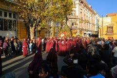 Penitents носят красные клобуки для традиционного Стоковая Фотография