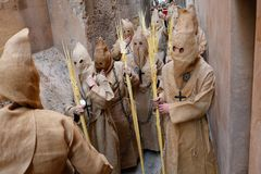 Penitents wait on queue before the start of an easter holy week procession in mallorca detail on hoods wide. Penitents prepare in a narrow street before taking royalty free stock photos