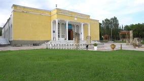Penjikent Rudaki History Museum 96. Penjikent Rudaki Republican Historical Museum Side View with Waving Tajikistan Flag on a Cloudy Blue Sky Day stock footage