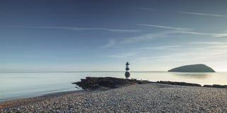 Penmon灯塔和大理石海滩在日出 库存图片