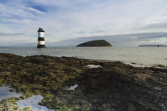 Penmon Beach, Anglesey, Wales. Lighthouse and Puffin Island. Pebbled beach looking to small lighthouse and island. Penmon, Anglesey, Wales, United Kingdom Stock Image