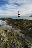 Penmon Beach, Anglesey, Wales. Lighthouse and Puffin Island. Pebbled beach looking to small lighthouse and island. Penmon, Anglesey, Wales, United Kingdom Stock Photo