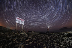 Penmon lighthouse at night with star trails Stock Images
