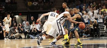 Penn State's D. J. Newbill is defended by Michigan's Trey Burke. As he drives Royalty Free Stock Photos