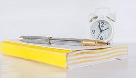 penna, anmärkning och klocka på den wood tabellen royaltyfri bild
