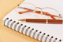 Penna, anteckningsbok och exponeringsglas Selektiv fokus på penna Arkivbild