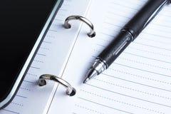 Penna, anteckningsbok och mobiltelefon Royaltyfria Foton