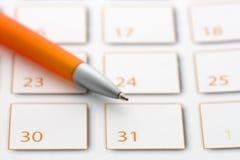 Penna arancione sul calendario 3 Fotografie Stock Libere da Diritti