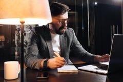 Penna barbuta della tenuta del project manager a disposizione e per mezzo del taccuino contemporaneo Giovane uomo d'affari che la Fotografia Stock Libera da Diritti