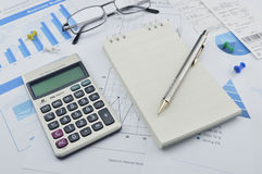 Penna, calcolatore e taccuino sul grafico e sul grafico finanziari, accou Immagini Stock Libere da Diritti