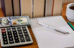 Penna con il blocco note, i dollari ed il calcolatore sui precedenti dei libri fotografia stock