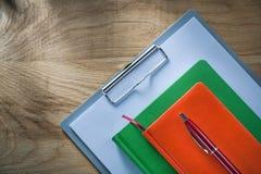 Penna d'annata del biro dei taccuini della lavagna per appunti sul bordo di legno fotografia stock