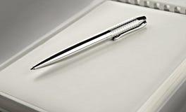 Penna d'argento sul taccuino Immagini Stock Libere da Diritti