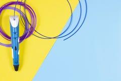 penna 3d med den färgglade plast- glödtråden på blått- och gulingbakgrund Arkivfoton