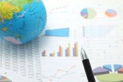 Penna davanti al globo ed alle carte con i numeri ed i grafici Fotografie Stock Libere da Diritti