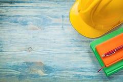 Penna dei blocchi note del casco della costruzione sul concep della costruzione del bordo di legno Fotografia Stock