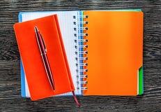 Penna del biro dei blocchi note sul punto di vista superiore del bordo di legno immagine stock