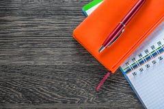 Penna del biro dei taccuini sul punto di vista superiore del bordo di legno fotografie stock