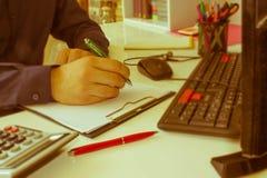 Penna del primo piano sui conti di lavoro di ufficio con il computer di uso dell'uomo per conservare i dati nel fondo Concetto di Immagini Stock