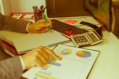 Penna del primo piano sui conti di lavoro di ufficio con il computer di uso dell'uomo per conservare i dati nel fondo Concetto di Fotografie Stock Libere da Diritti