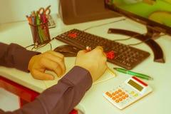 Penna del primo piano sui conti di lavoro di ufficio con il computer di uso dell'uomo per conservare i dati nel fondo Concetto di Fotografia Stock Libera da Diritti