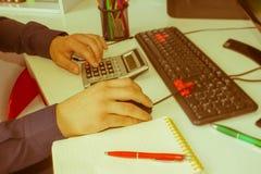 Penna del primo piano sui conti di lavoro di ufficio con il computer di uso dell'uomo per conservare i dati nel fondo Concetto di Fotografia Stock