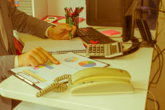 Penna del primo piano sui conti di lavoro di ufficio con il computer di uso dell'uomo per conservare i dati nel fondo Concetto di Immagine Stock