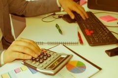 Penna del primo piano sui conti di lavoro di ufficio con il computer di uso dell'uomo per conservare i dati nel fondo Concetto di Immagine Stock Libera da Diritti