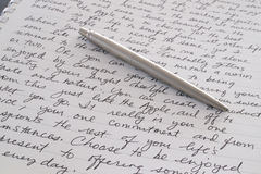 Penna dell'acciaio inossidabile che pone alla pagina scritta fotografie stock