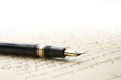 Penna dell'oro con la lettera e la scrittura Immagine Stock