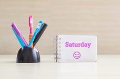 Penna di colore del primo piano con lo scrittorio ceramico nero ordinato per la penna e la parola di sabato di porpora in pagina  Fotografia Stock Libera da Diritti