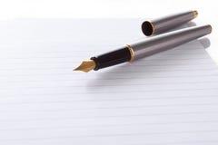 Penna di fontana che si trova alla pagina in una spirale - notep rilegato Immagine Stock Libera da Diritti