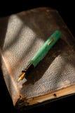 Penna di fontana dell'annata sulla vecchia bibbia Immagini Stock