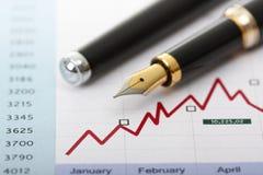Penna di fontana sui diagrammi e sul grafico di affari Fotografia Stock