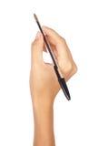 Penna di holding della mano isolata sopra bianco Fotografia Stock