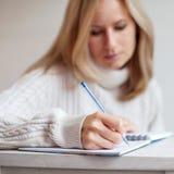 Penna di scrittura della donna in taccuino Fotografia Stock Libera da Diritti