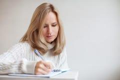 Penna di scrittura della donna in taccuino Fotografie Stock Libere da Diritti