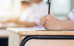 Penna di tenuta degli studenti in mani che prendono gli esami, scriventi esame immagine stock libera da diritti