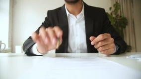 Penna di tenuta dell'uomo d'affari che indica sul contratto, offrente al documento del segno video d archivio