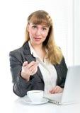 Penna di tenuta della donna di affari che si siede allo scrittorio Fotografia Stock