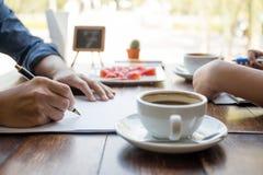 Penna di tenuta della mano degli uomini sopra la forma di accordo con il caffè della tazza Fotografie Stock