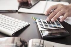 Penna di tenuta della mano dell'uomo di affari facendo uso del calcolatore e documenti sulla scrivania con il computer portatile  fotografie stock libere da diritti