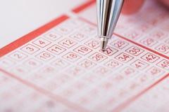 Penna di tenuta della persona sopra il biglietto di lotteria Fotografie Stock Libere da Diritti