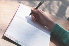 Penna di tenuta femminile della mano sopra il taccuino con lo spazio della copia immagine stock