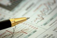 Penna dorata che mostra schema sul rapporto finanziario Immagine Stock