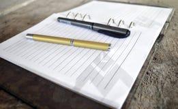 Penna dorata sul taccuino Immagine Stock