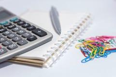 Penna e calcolatore del cavo sul libro Immagine Stock